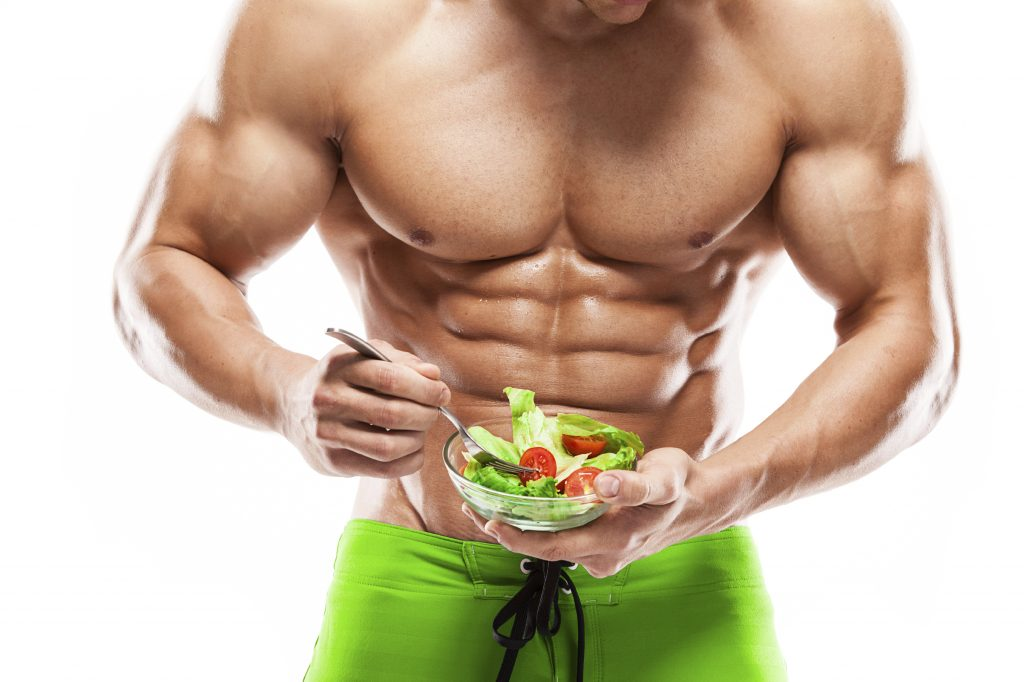 Shaped and healthy body man holding a fresh salad bowl,shaped ab